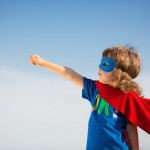 Superhero kid against blue sky background. Girl power concept